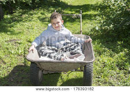 Spring in the garden bright sunny day sitting on a wheelbarrow a little funny curly boyl.