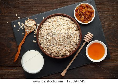 Ingredients For Oatmeal On Rustic Wooden Background: Rolled Oat Flakes, Milk, Honey And Raisins.