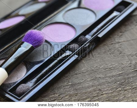 Makeup brush and eye shadow palette on old wooden background with copy space.Various make-up products.Fashion cosmetic makeup or woman beauty accessories concept.Selective focus.