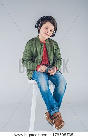 Cute Smiling Boy In Headphones Sitting On Stool And Using Smartphone
