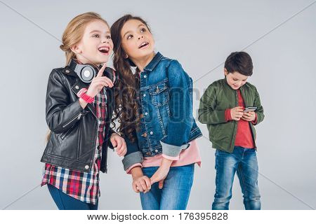 Two Cute Smiling Girls Looking Up While Boy Using Smartphone