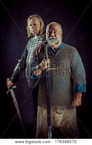 Two Powerful Knights With The Swords On The Dark Background