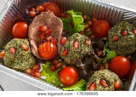Healthy eating, diet food delivery concept. Lunch foil box, take away organic restaurant dishes. Falafel with pomegranate and salad on white wood, closeup