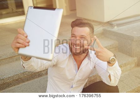 Man freelancer making selfies with tablet PC during break. Smiling bearded man showing yo sign for the camera outdoors. Toned image.