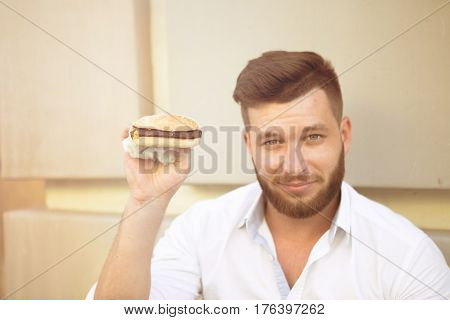 Handsome man going to eat hamburger. Bearded hipster in white shirt having break. Close-up of delicious hamburger with beef. Toned image.