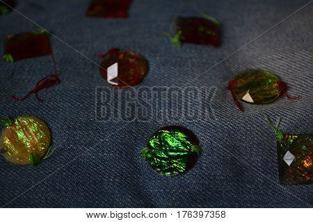 denim fabric sewn into her multi-colored stones