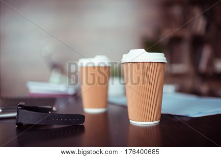 Close-up view of smartwatch and disposable coffee cups on table