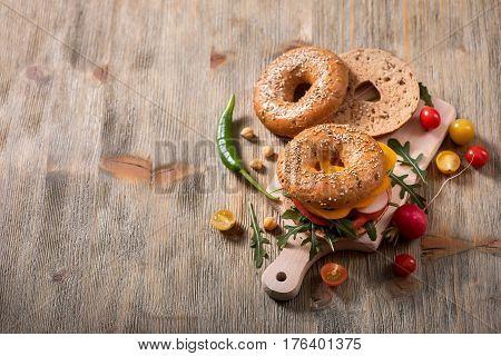 Vegan bagel sandwich with fresh veggies and arugula vegetarian healthy food lunch breakfast snack copy space background