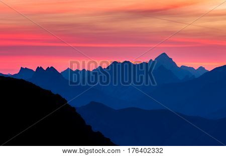 Majestic blue mountain ranges silhouettes with pink violet clouds. Sunrise in early morning. Tirol, Austria, Alps.