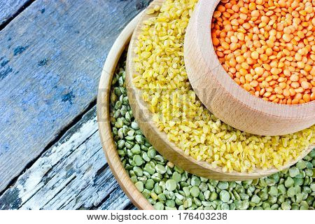 Colorful cereals - red lentils yellow bulgur and green peas blank space for text