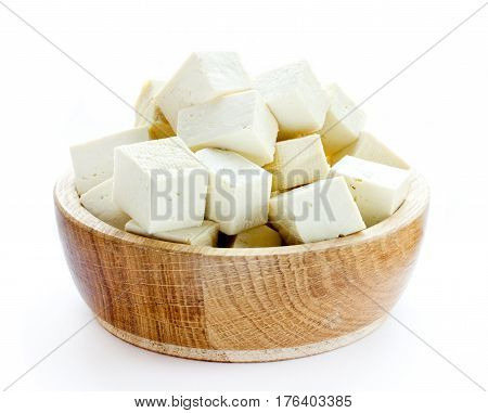 Tofu cubes in wooden bowl isolated on white background