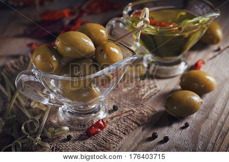 Premium extra virgin olive oil and green olives with fresh herbs black pepper and chile pepper on rustic wooden background.
