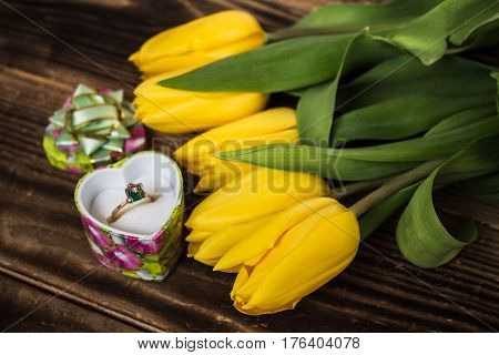 yellow tulips and engagement ring on wooden background