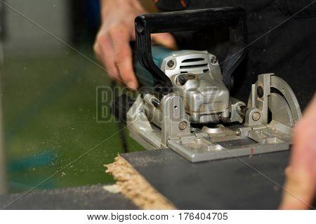 Closeup on carpenter's hands using sawing machine