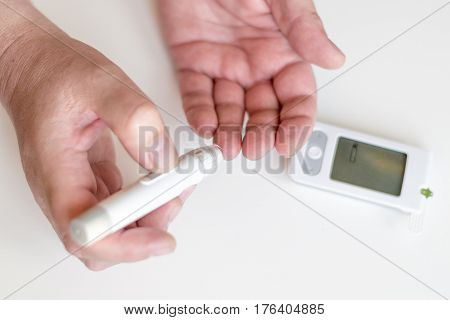 Medicine, Diabetes, Glycemia, Health Care And People Concept - Close Up Of Man Hands Using Lancet On