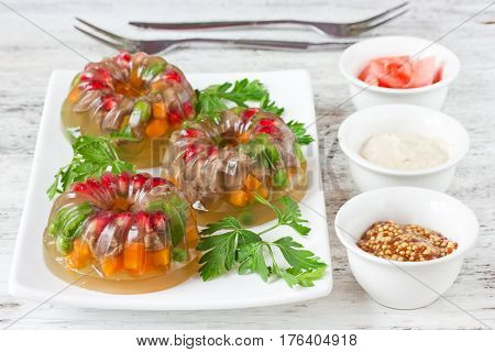 Aspic from meat with green peas carrot pomegranate parsley. Cold appetizer festive snack meat jelly with vegetables selective focus