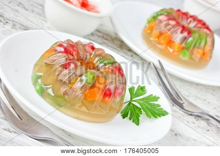 Festive jellied meat with vegetables carrot peas corn pomegranate parsley selective focus