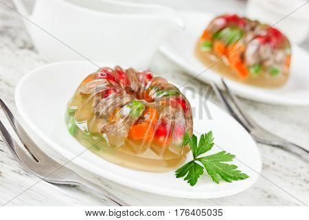 Aspic decorated with pomegranate green peas carrot and parsley. Restaurant dish for a celebratory feast selective focus