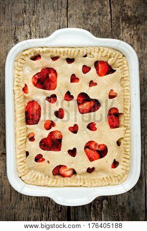 Strawberry cake with heart decoration. Shortcrust dough summer fruit pie preparation concept top view