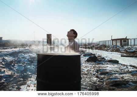 BELGRAD-EINFORMAL REFUGE CAMP-JAN 2017--A person washing himself from a barrel with hot water outside a warehouse that has served as a makeshift shelter on January 2, 2017 in Belgrade, Serbia