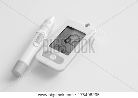Medicine, diabetes, glycemia, health care and people concept - Glucose meter with result and lancet device for the diagnosis of glucose