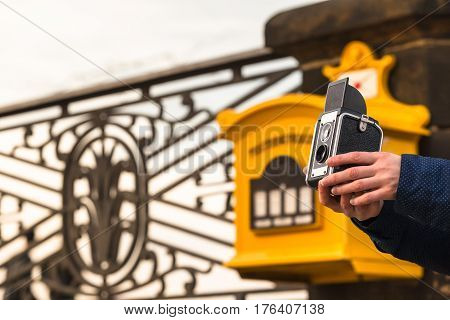 Hand of unrecognizable woman hold an old camera in front of yellow antique german mailbox and ornamented handrail