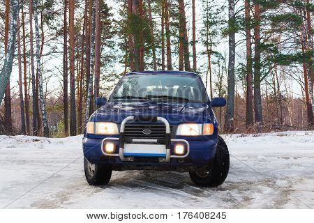 Blue off-road car standing in the woods in the winter