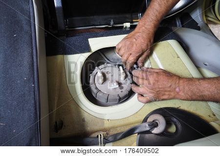 Service man pull off pump tik fuel to change a new one in my small size car fisrt step focus select at object cover finger are moving blur.