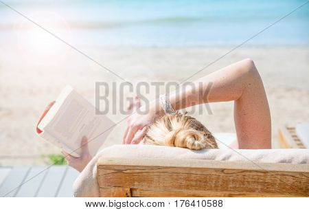 Young caucasian woman lying on wooden pier on the sea reading book and taking sun bath enjoying perfect summer day traveling and luxury vacation or skin care beauty concept focus on arm copy space