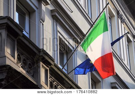 Italian and European flags on municipal building facade.