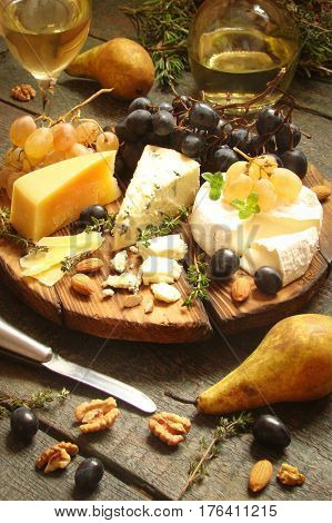 cheese platter Parmesan. Camembert Gorgonzola with grapes and nuts aromatic herbs on wooden background