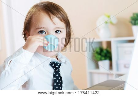 Toddler Girl Drinking From A Mug In Front Of A Laptop