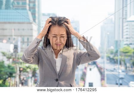 Portrait of a stressed young businesswoman holding head in hands standing outdoor with the background of urban landscape. Unhappy Asian girl with worried stressed face expression looking down.