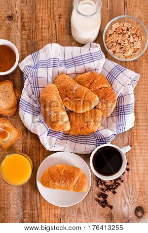 Breakfast with croissants and orange juice on wooden table.