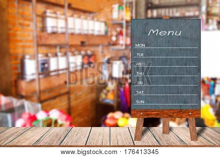 Wooden menu display sign A Frame restaurant message board on wooden table Blurred image background Template mock up for adding your design and leave space beside frame for adding more text.