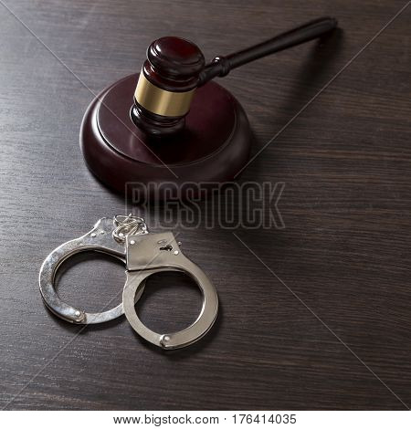 Close up of a judge gavel and handcuffs in a courtroom. Selective focus