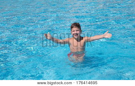 Little boy catching the ball in the pool, space for text, outdoor shooting