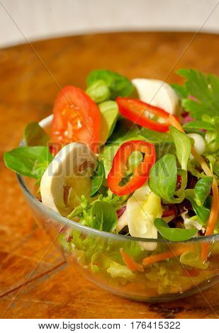 Tasty fresh salad on wooden table, close up