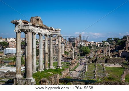 Buildings and ruins, Roman Forum. Rome, Italy - April 20, 2015: High angle view of tourists walking at Roman forum in Rome looking at ancient buildings and ruins, Temple of Saturn in the foreground.