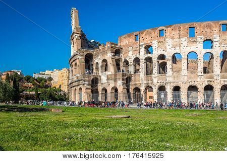 Colosseum in Rome. Rome, Italy - April 20, 2015: Exterior ground view of ancient Colosseum in Rome with many tourists who comes and goes outside. A few horses and carriage outside for transportation.