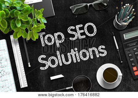 Black Chalkboard with Handwritten Business Concept - Top SEO Solutions - on Black Office Desk and Other Office Supplies Around. Top View. 3d Rendering.