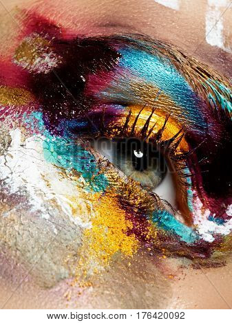 Beauty cosmetics and makeup. Magic eyes look with bright creative make-up. Macro shot of beautiful woman's face with perfect art make up. Closeup of female eye. Body art