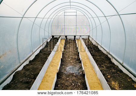 Greenhouse made of polycarbonate inside early spring. Three beds.