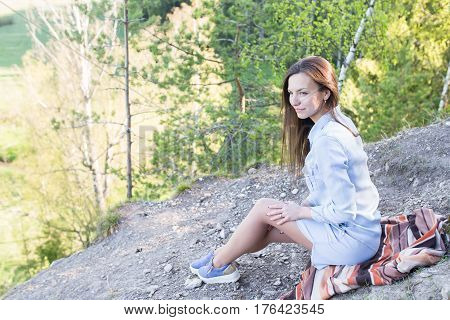 Portrait of a beautiful young woman on a rock precipice of a mountain in the forest. Freedom, independence and relaxation concept.