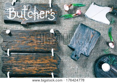 Dark wood boards as frames on burlap background with cutting tools, onions and salt. Wooden signboard with text 'Butchers' as title bar. Rustic style template for food and drink industry