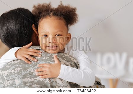 Mommy is back. Gorgeous positive curly child hugging her mother expressing her happiness after missing her very much