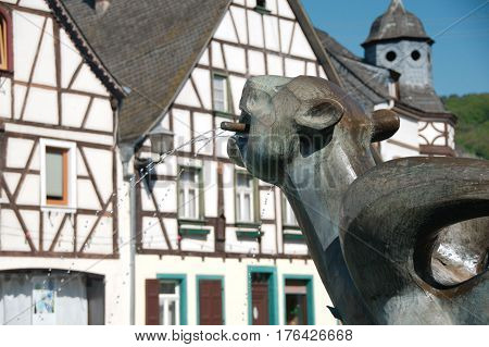 Tatzelwurm fountain statue with an old half-timbered house in Kobern-Gondorf Germany