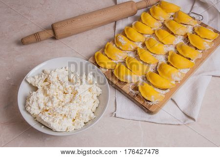 Ready For Boiling Vareniki, Dumplings, Pierogi On Wooden Cutting Board With Flour And White Plate Wi