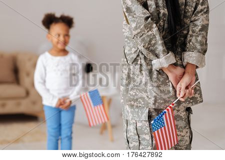 Welcome home. Lovely charismatic pretty girl waiting for her mom hugging her while standing in a living room and holding a flag in her hands