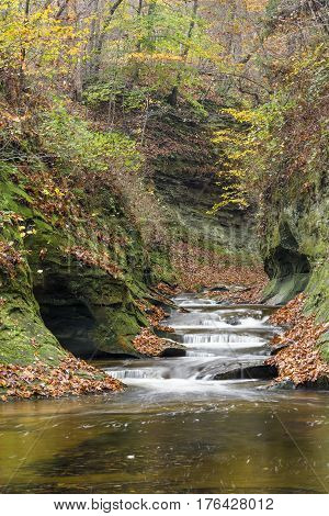 Water cascades down The Potholes a series of rocky ledges eroded by swirling currents in Fall Creek Gorge Warren County Indiana.